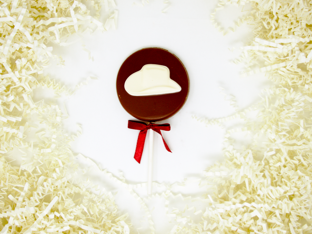 white cowboy hat lollipop with milk chocolate and red ribbon