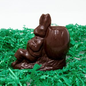 napping peter rabbit hollow chocolate sculpture leaning against a barrell