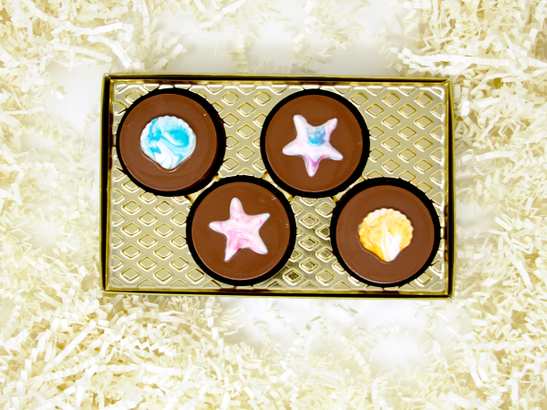 four colorful chocolate covered oreos decorated with seashells